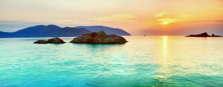 Заставки одинокое судно, скалы в море, солнце из-за туч, закат