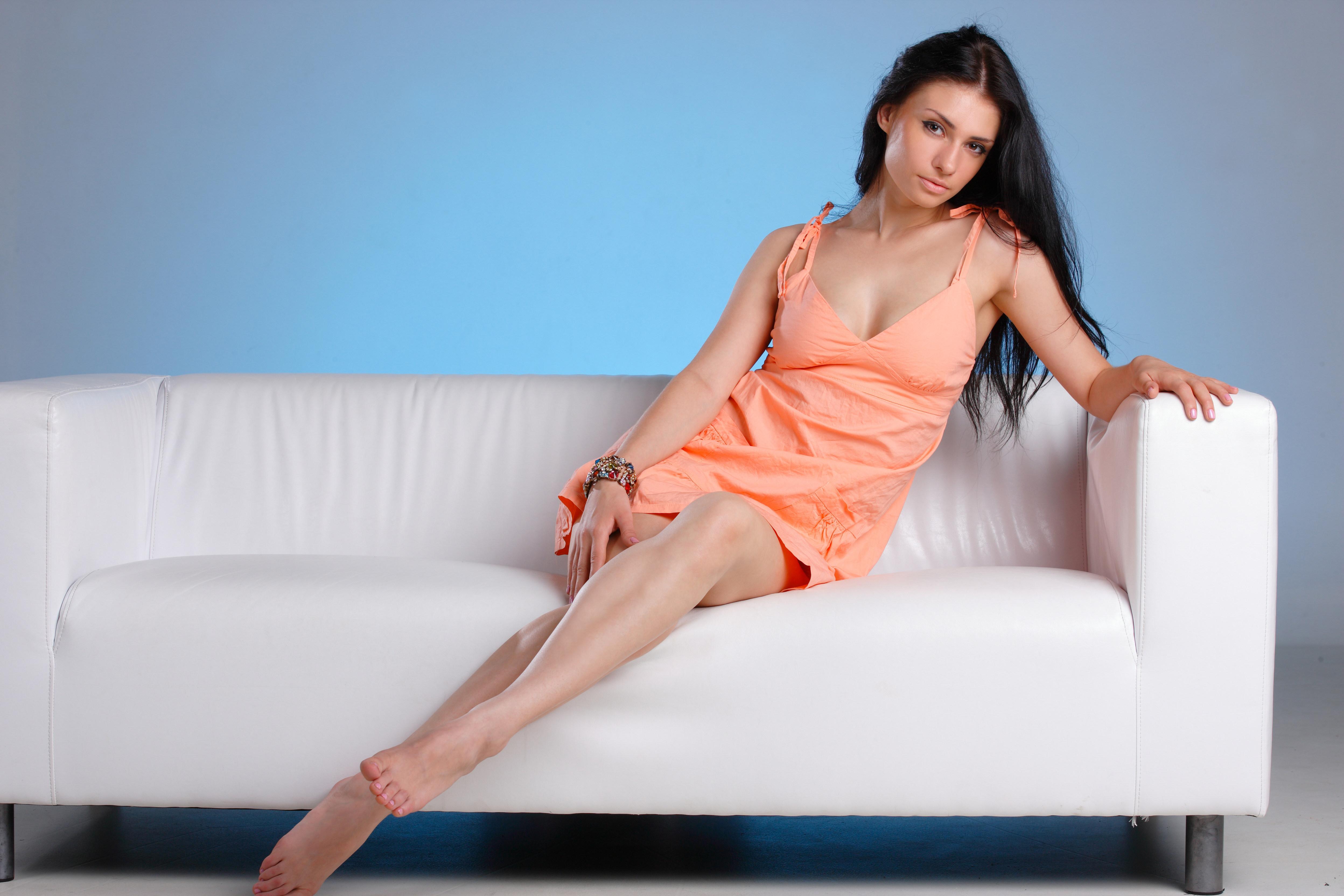 Девушка красивая сидит на диване